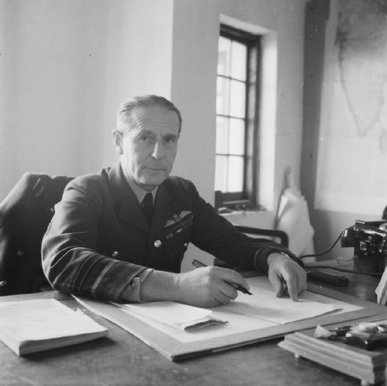 Half length portrait of Air Chief Marshal Philip Joubert de la Ferte, Deputy Chief of Staff for Information and Civil Affairs, South East Asia Command, seated at his desk