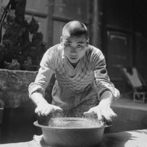 "A temple boy moves his hands over an ancient bronze bowl to make it ""sing"" and spray water"