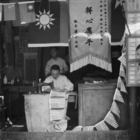 An enterprising Chinese craftsman sewing a string of small American flags in his shop in Chengtu