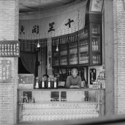 A Chengtu wine shop; the shopkeeper leans on the counter surrounded by his wares