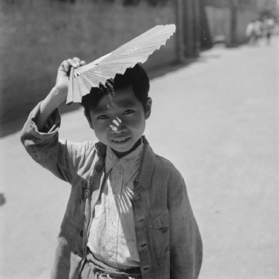 A small boy posing with his fan above his head in Chengdu