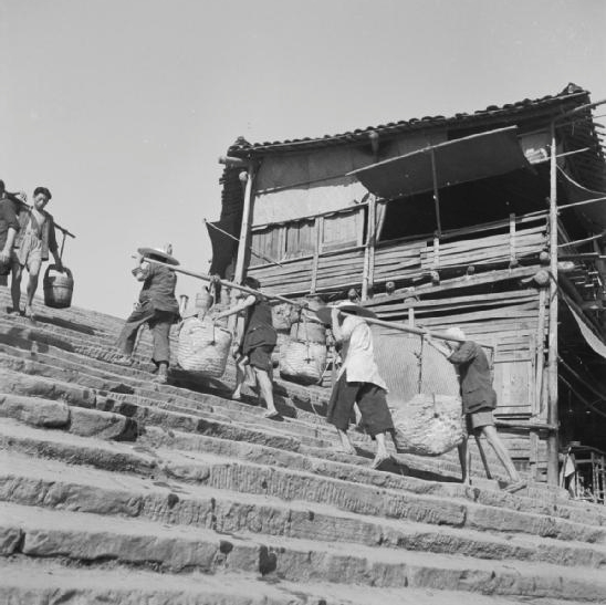 Four coolies carry their loads on a single pole up the wharfside steps at Chungking