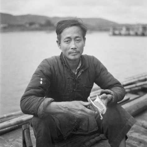 A river coolie sitting in a ferry boat in south eastern China