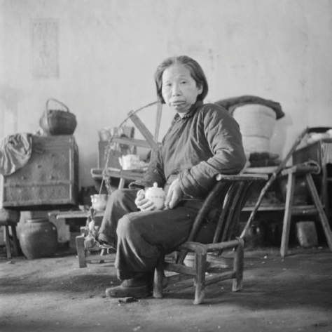 An old woman seated on a small chair clutching a teapot in the Poor People's Refuge in Changsa