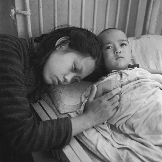 A mother resting her head on her sick child's pillow in the Canadian Mission Hospital in Chengdu